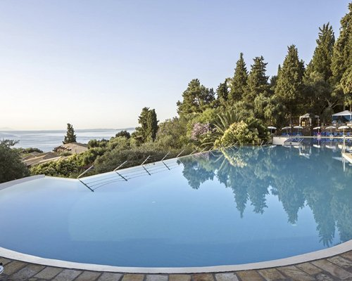 Outdoor swimming pool with view alongside wooded area.