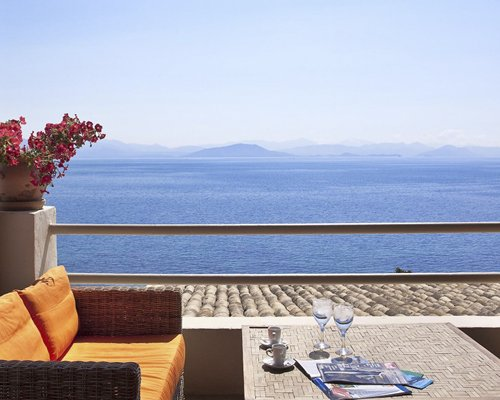 Balcony lounge area with a view of the sea and distant mountains.