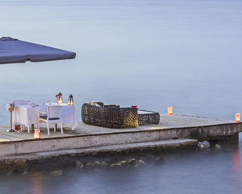 Outdoor dining on a pier surrounded by ocean.