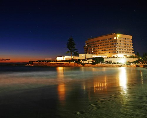 A beach view of multi story resort units at night.