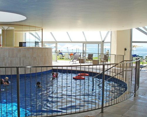 Indoor swimming pool with an outside view.