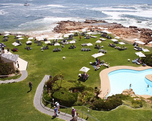 A groomed lawn with umbrellas and chairs alongside a pool and the seashore.