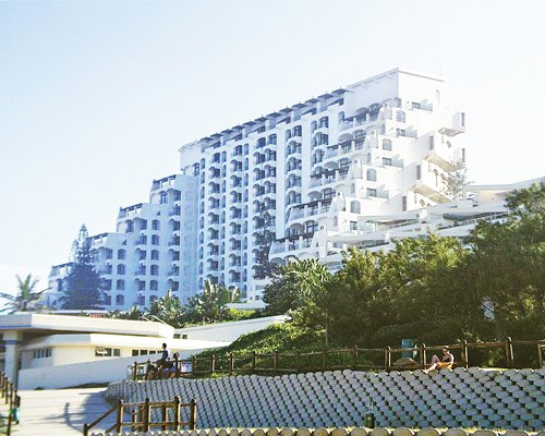 An exterior view of multi story resort units surrounded by trees.