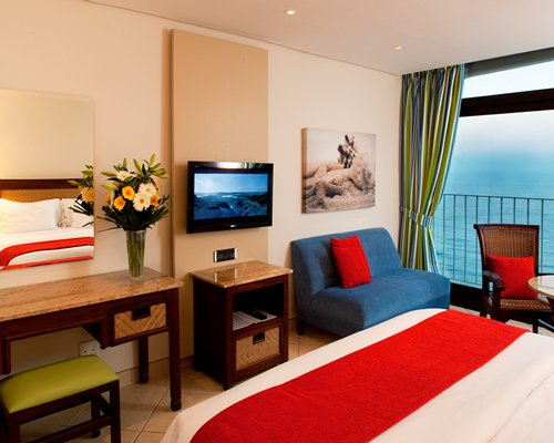 A well furnished bedroom with a television and ocean view.