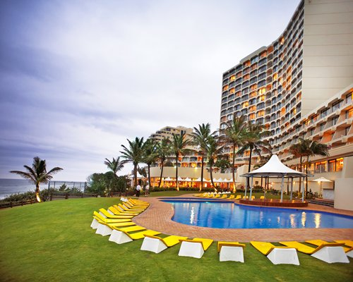 Umhlanga Sands outdoor swimming pool with chaise lounge chairs along the beach.