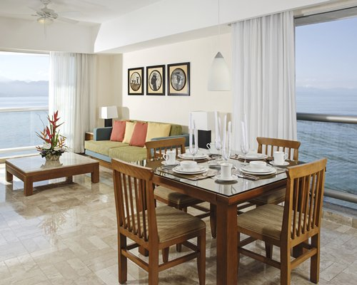 A well furnished living room with a dining area and ocean view.