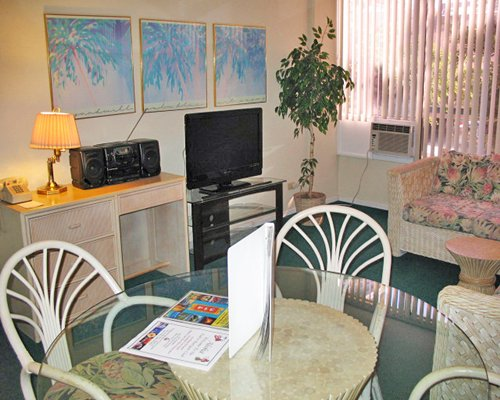 A well furnished open plan living and dining area with a television.