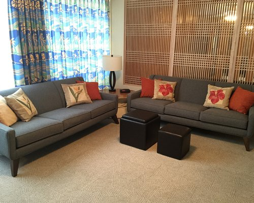 A well furnished living room with a double pull out sofa and an ottoman.