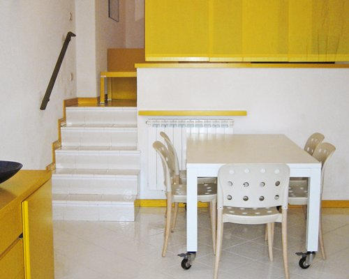 A well furnished dining table alongside a stairway.