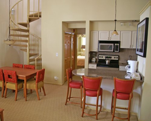 A well equipped kitchen with a dining table and breakfast bar alongside the staircase.