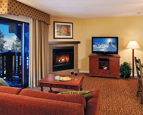 A well furnished living room with a television dining area balcony and fire in the fireplace.