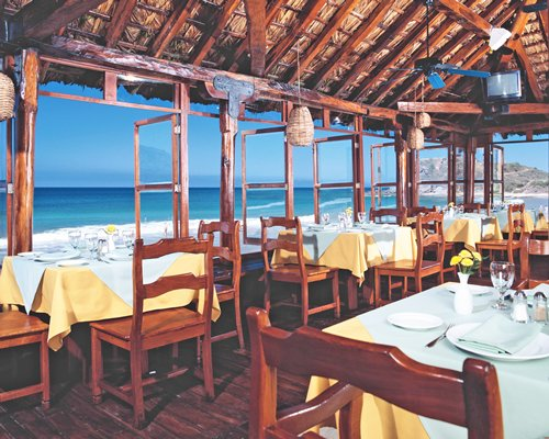 A well furnished indoor restaurant with a beach view.