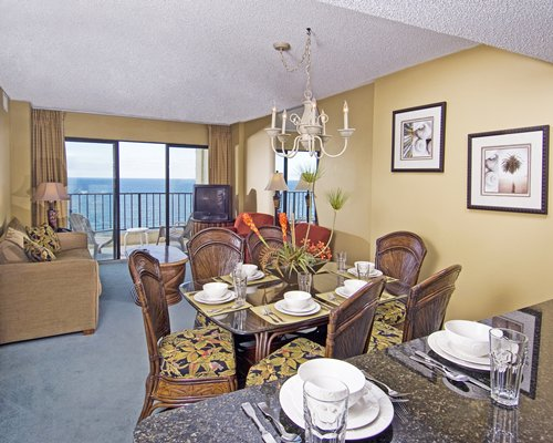 An open plan living and dining area with a television balcony and patio furniture.