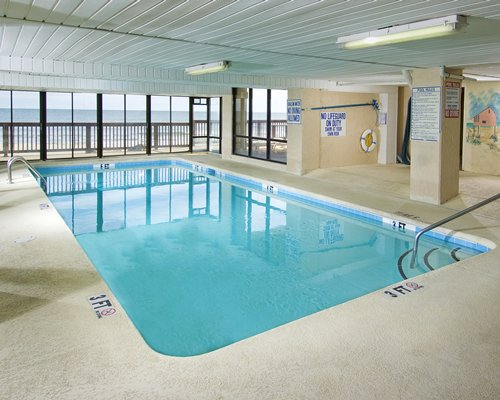 An indoor swimming pool with an ocean view.