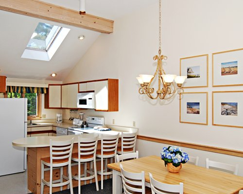 A well equipped kitchen with a breakfast bar and dining area.