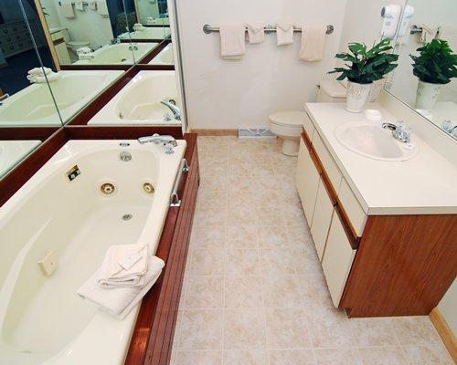A bathroom with bathtub and single sink vanity.
