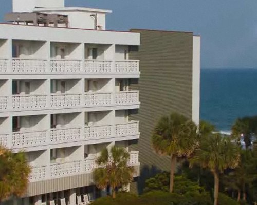 Scenic exterior view of multiple unit balconies alongside the beach.