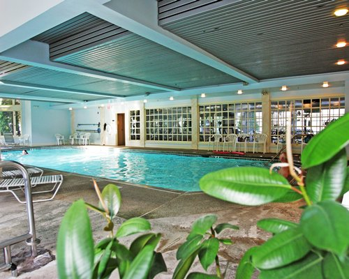 An indoor swimming pool with chaise lounge chairs and patio furniture.