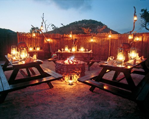 A campfire surrounded by picnic tables with candle lights.