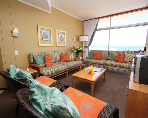 A well furnished living room with a television and a beach view.