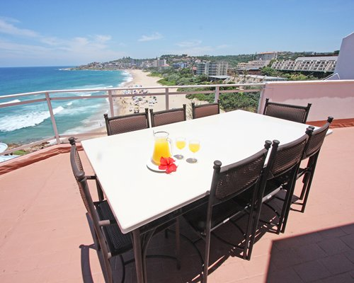 A dining table in the balcony with a beach view.