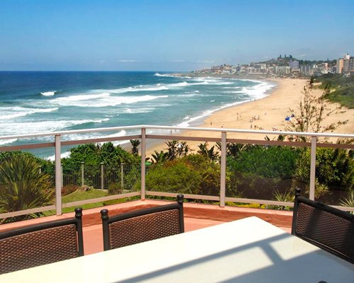 A dining table on the balcony with a beach view.