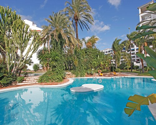 A scenic outdoor swimming pool alongside the Jardines del Puerto resort.