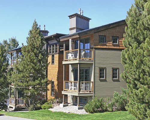 An exterior view of the multi story resort units with pine trees.