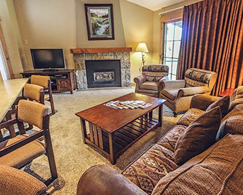 A well furnished living room with dining area television and fireplace.