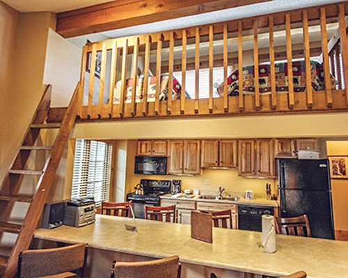 A well equipped kitchen with breakfast bar alongside the wooden staircase.