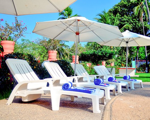 Scenic view of chaise lounge chairs and thatched sunshades.