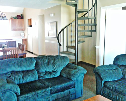 A well furnished living room with a dining area open plan kitchen and spiral stairway.