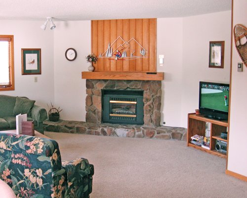 A well furnished living room with television and a fireplace.