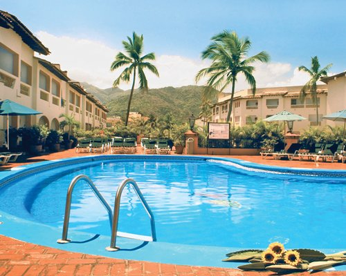 An outdoor swimming pool with chaise lounge chairs and sunshades alongside the resort units.