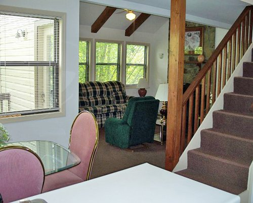A well furnished dining room with a stairway alongside a living room.