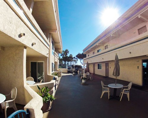 View of units at Southern California Beach Club with outdoor patio and patio chairs.
