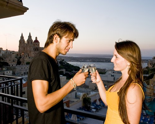 A couple having champagne at a balcony.