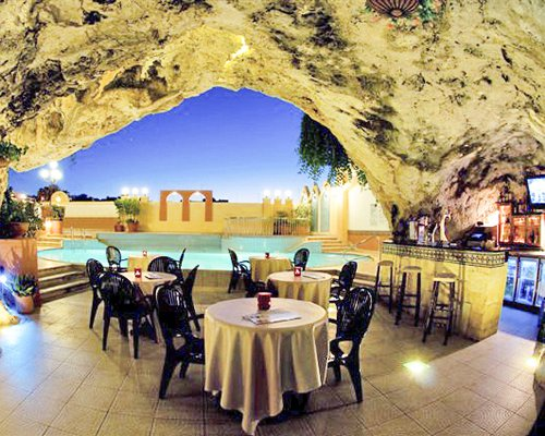 A well furnished indoor restaurant with a bar in a cave alongside a swimming pool.