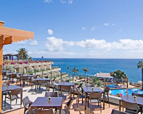 An outdoor fine dining area alongside the resort and the ocean.