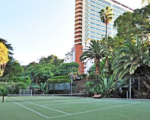 An outdoor tennis courts surrounded by trees alongside multi story resort units.