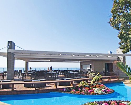 Outdoor restaurant alongside swimming pool with ocean view and landscaping.