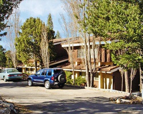 A street view of multi story resort units alongside trees.