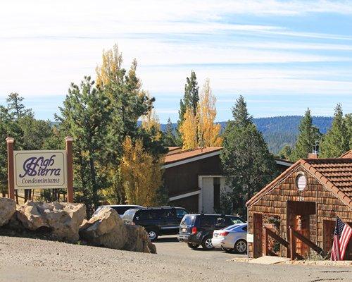 A street view of resort units alongside trees.