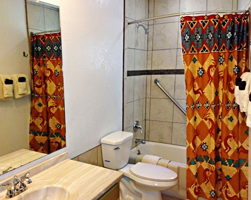A bathroom with a single sink vanity and a bathtub.