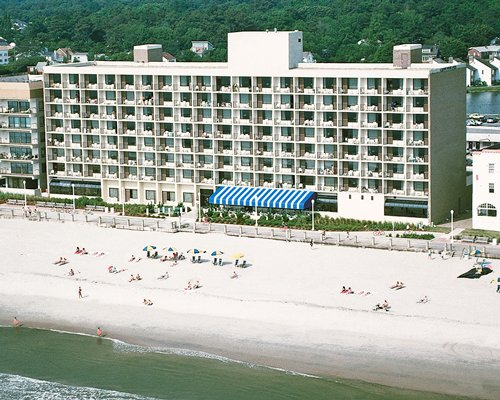 An aerial view of multi story resort alongside the beach.