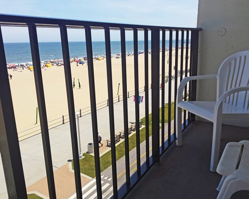 A balcony with patio furniture and a view of the beach.