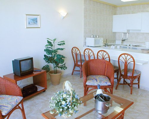A well furnished living room with a television alongside kitchen with a breakfast bar.