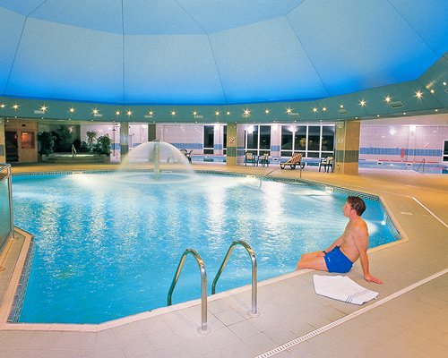 An indoor swimming pool with water fountain and patio furniture.