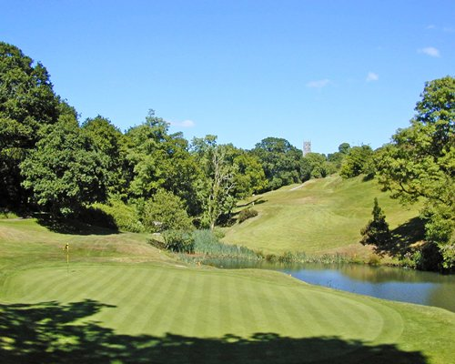 Golf course alongside a pond surrounded by wooded area.