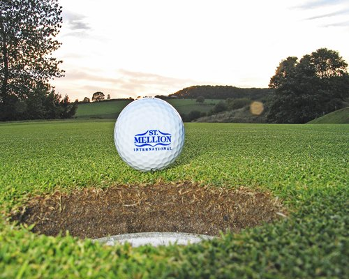 A St. Mellion golf ball next to the hole.